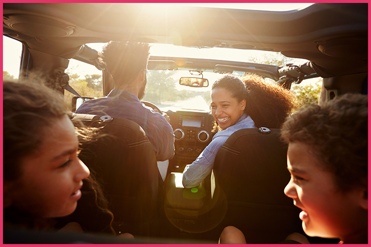 Mom looks back at her kids in card during a road trip; Courtesy Monkey Business Images/Shutterstock