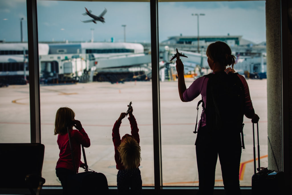 Mother and two children watching planes on the runway