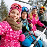 Family Taking Selfie on Ski Lift; Courtesy of Lucky Business/Shutterstock.com
