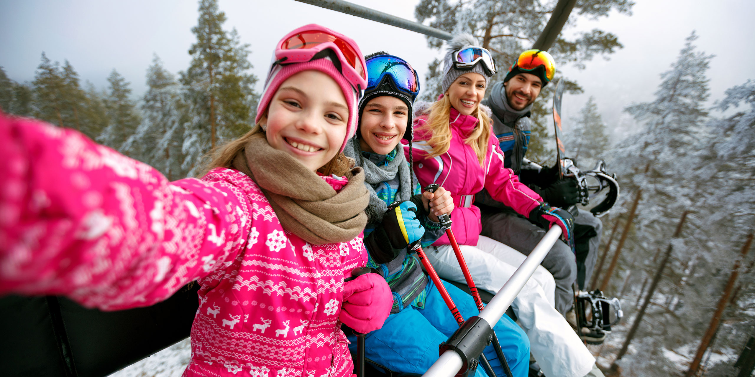Family Taking Selfie on Ski Lift; Courtesy of Lucky Business/Shutterstock.com