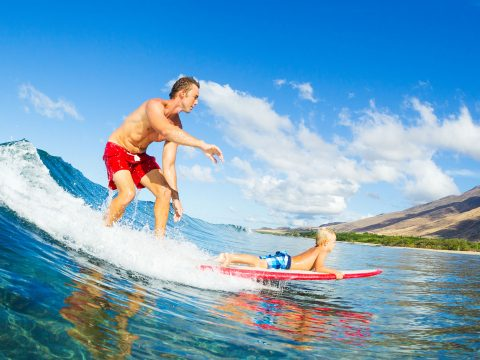 Father and Son Surfing in Hawaii; Courtesy of Epic Stock Media/Shutterstock.com