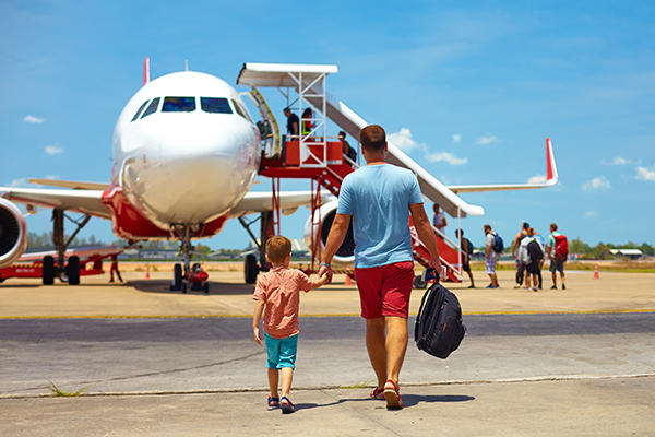 Father and son board a plane at the airport.