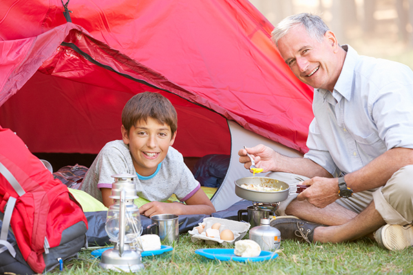 Grandfather and grandson cooking breakfast on a camping trip.