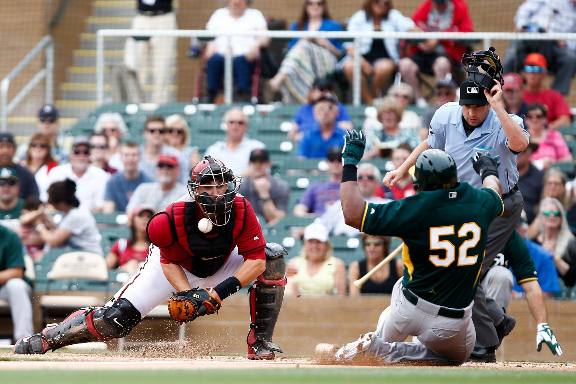 Arizona Diamondbacks catcher, Miguel Montero (26), misses the tag on Oakland Athletics left fielder, Yoenis Cespedes (52), at Salt River Fields at Talking Stick on March 6, 2014 in Scottsdale, Arizona.