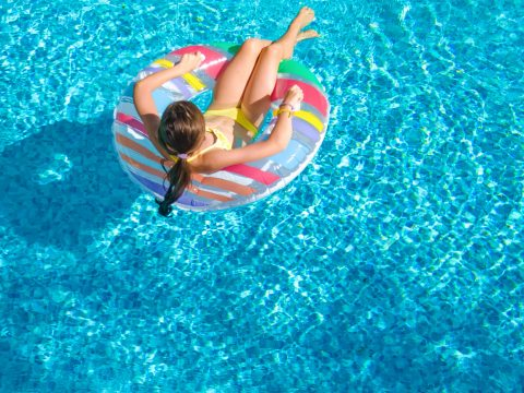 Girl in Hotel Pool; Courtesy of JaySi/Shutterstock.com