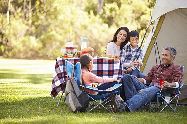 A family enjoying dinner on a camping trip.