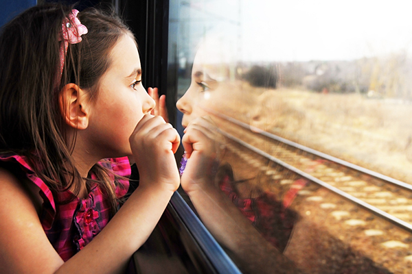 A little girl looking out the window of a train