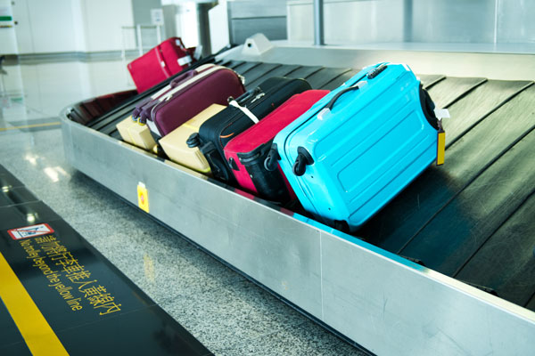 Suitcases on luggage belt at airport.