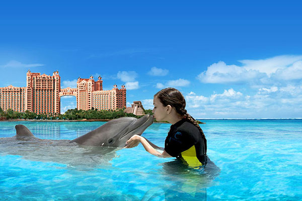 Young girl kissing a dolphin at Atlantis, Paradise Island in the Bahamas.