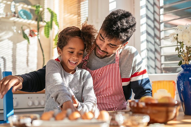 Smiling african american father and daughter baking in the kitchen; Courtesy of bbernard/Shutterstock