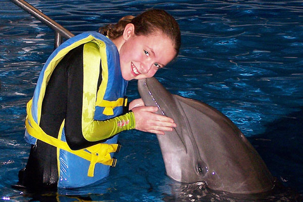 Little girl getting kissed by a dolphin.