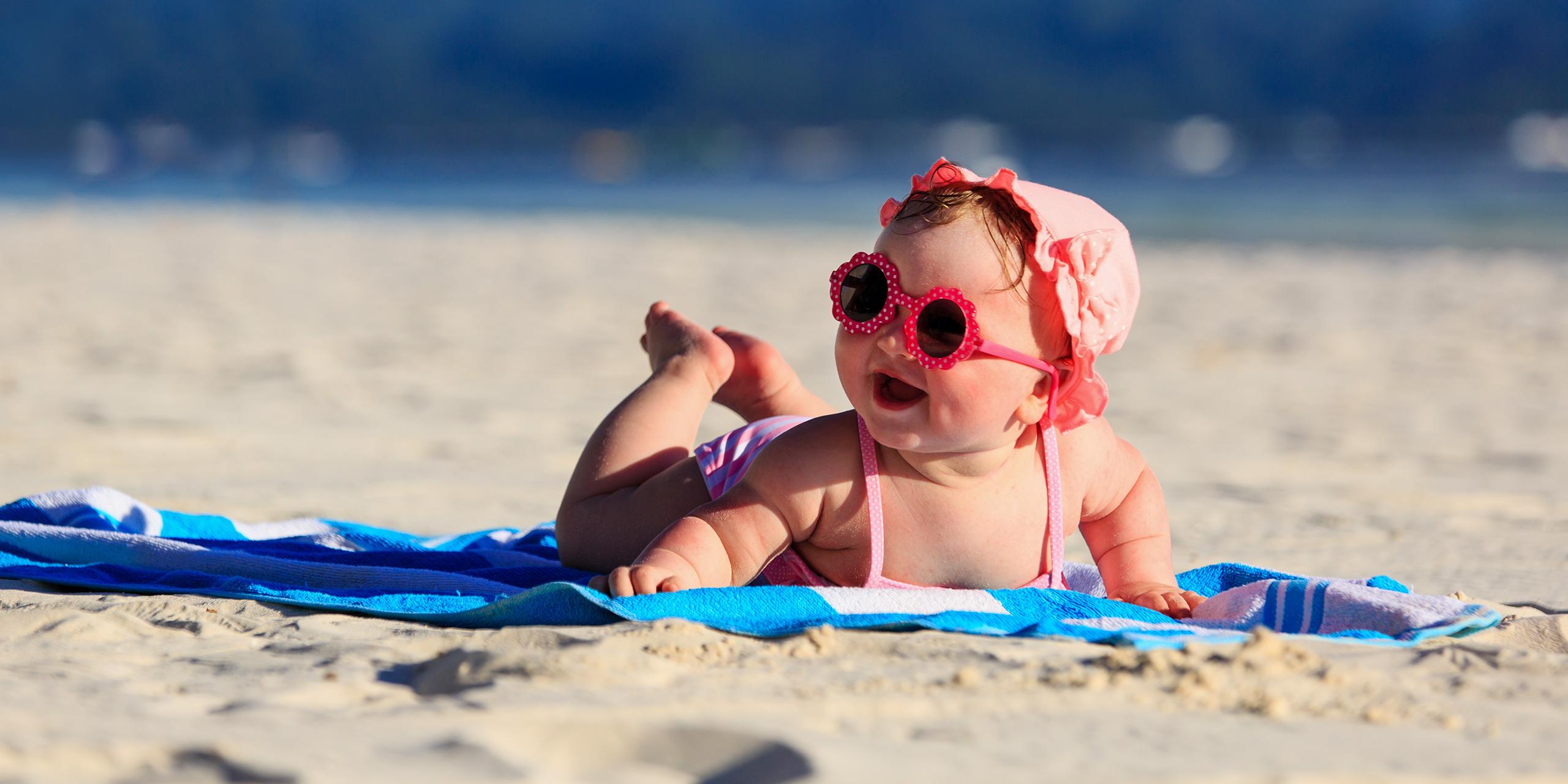 cute little baby girl on tropical sand beach ; Courtesy of NadyaEugene/Shutterstock