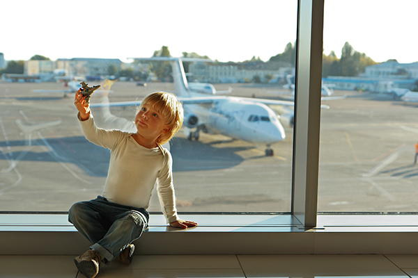 Little boy playing with a toy airplane at the airport