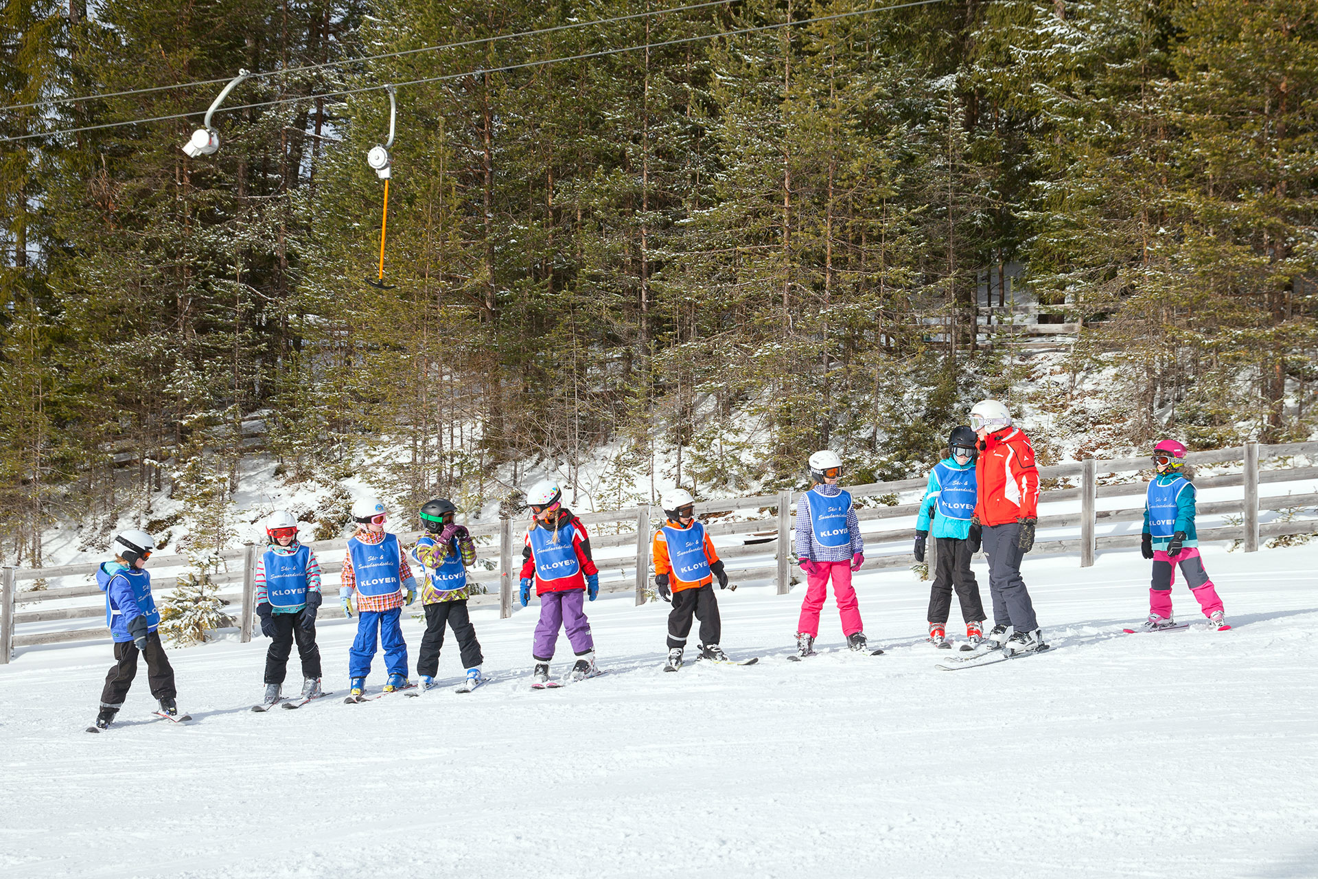 A group of kids getting a ski lesson.