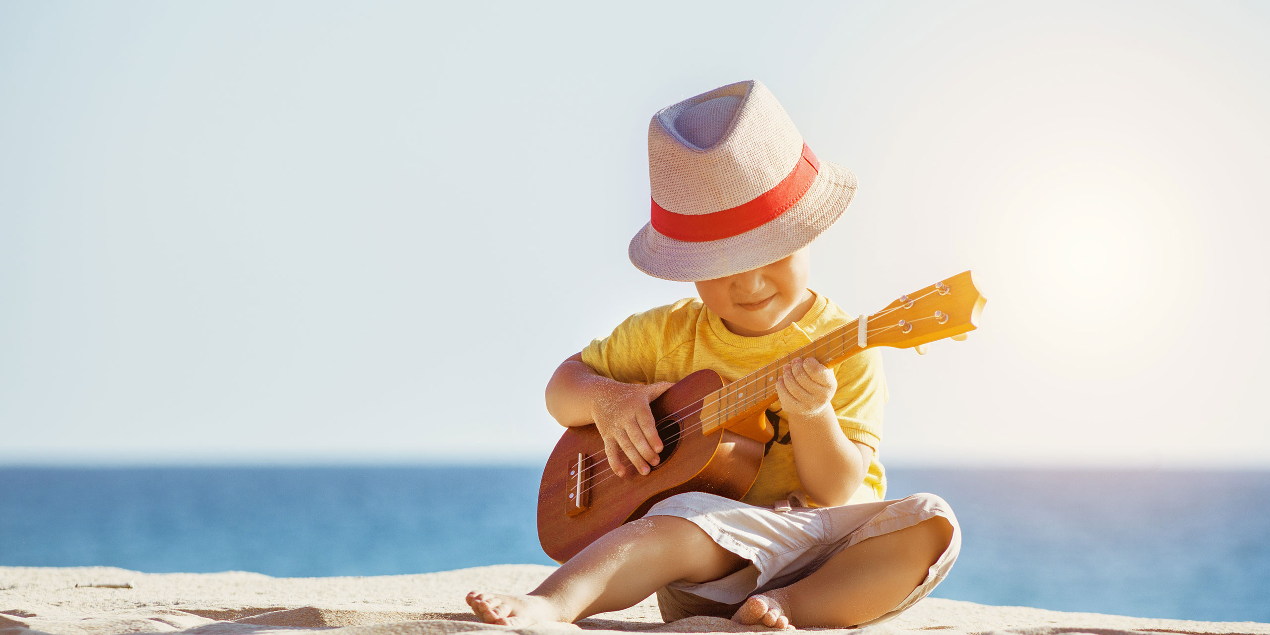Little Boy Playing Ukulele in Hawaii; Dmitry Molchanov/Shutterstock.com
