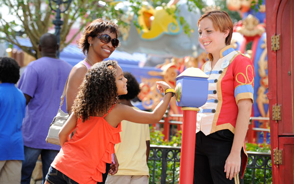 A girl using her MyMagic+ wristband to get onto a ride at Disney World.