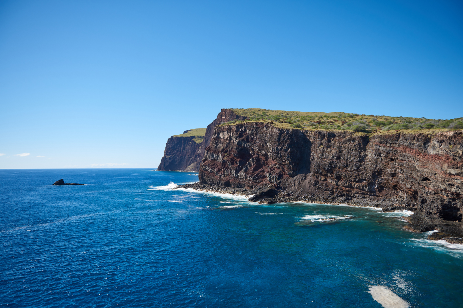 Photo of lanai island of Hawaii, water and cliffs, bright blue sky