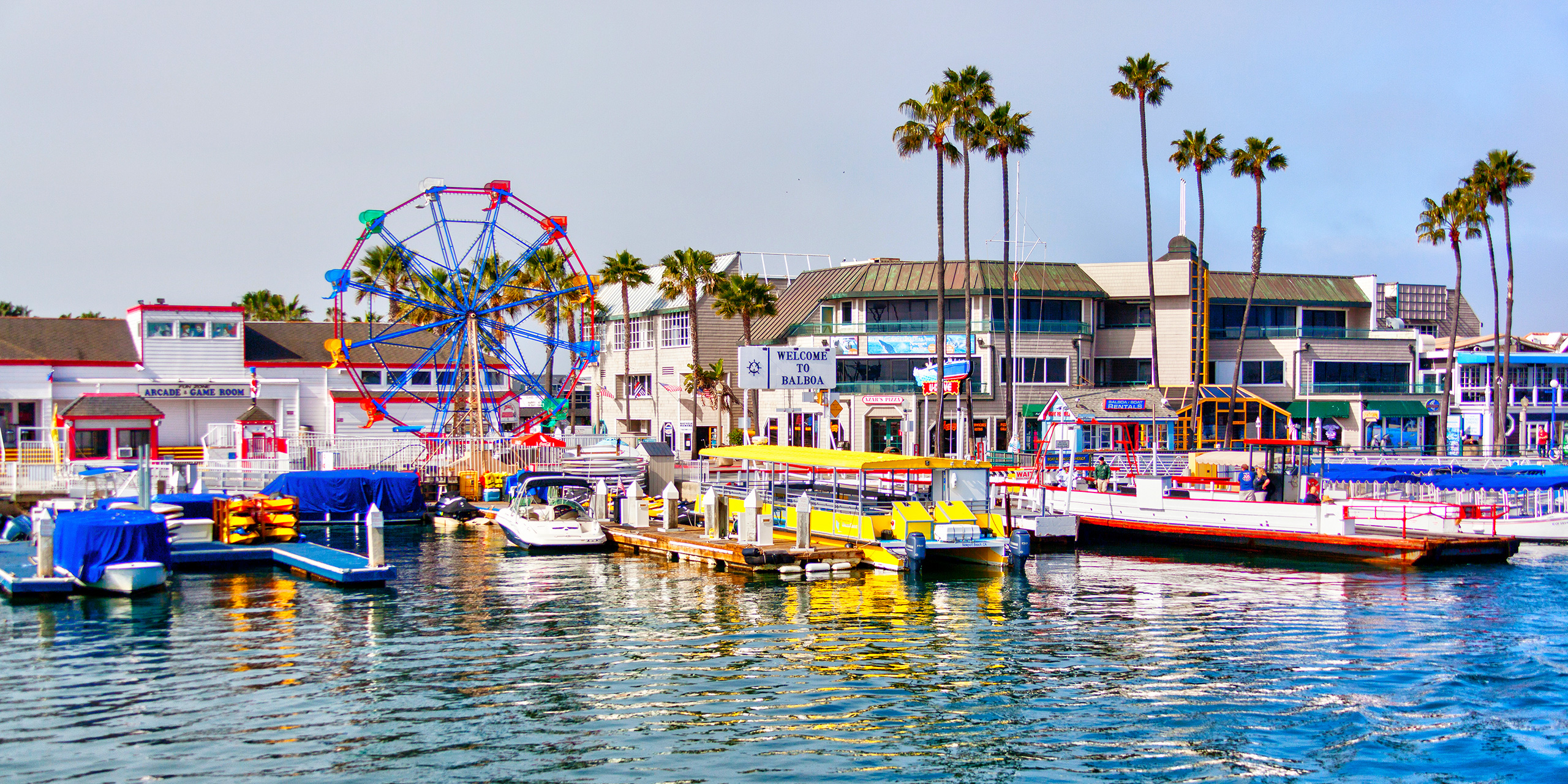 Popular pier at Balboa peninsula in Southern California with ferris wheel, tourist shops, restaurants and boats doting the harbor ferry terminal.; Courtesy of Ronnie Chua/Shutterstock