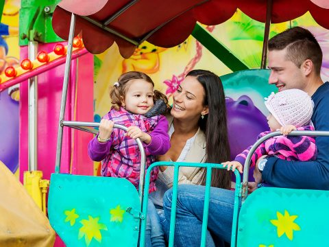 Father, mother, daughters enjoying fun fair ride, amusement park; Courtesy of Halfpoint/Shutterstock