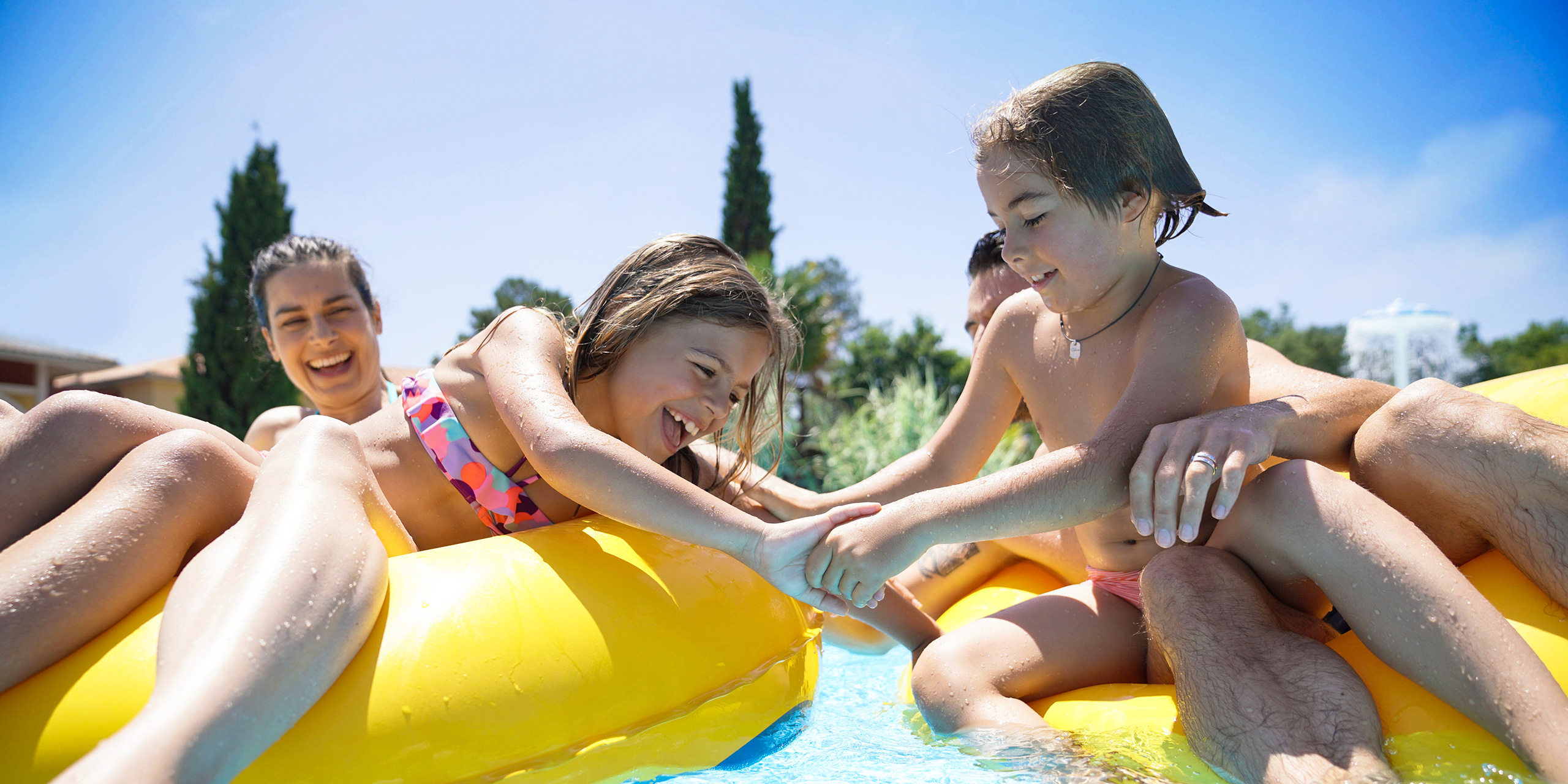 Family having fun riding inflatable ring at the pool; Courtesy of goodluz/Shutterstock