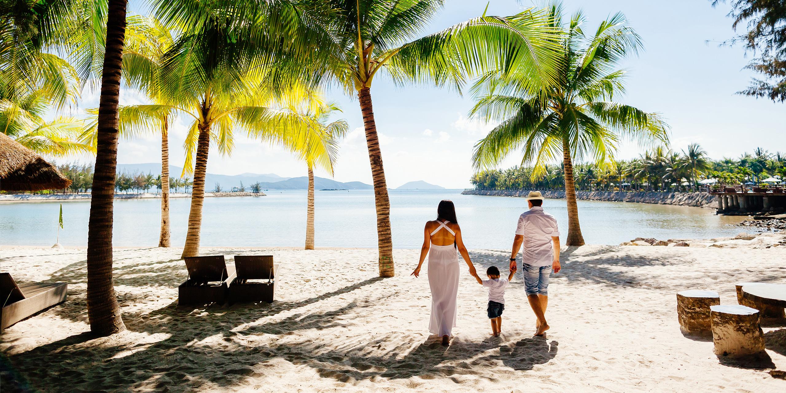 family walking along beach palm trees; Courtesy of shevtsovy/Shutterstock