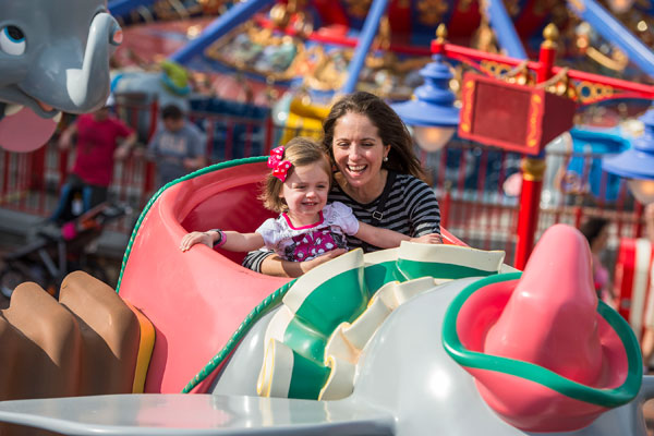 Mother and daughter ride Dumbo the Flying Elephant at Disney World.