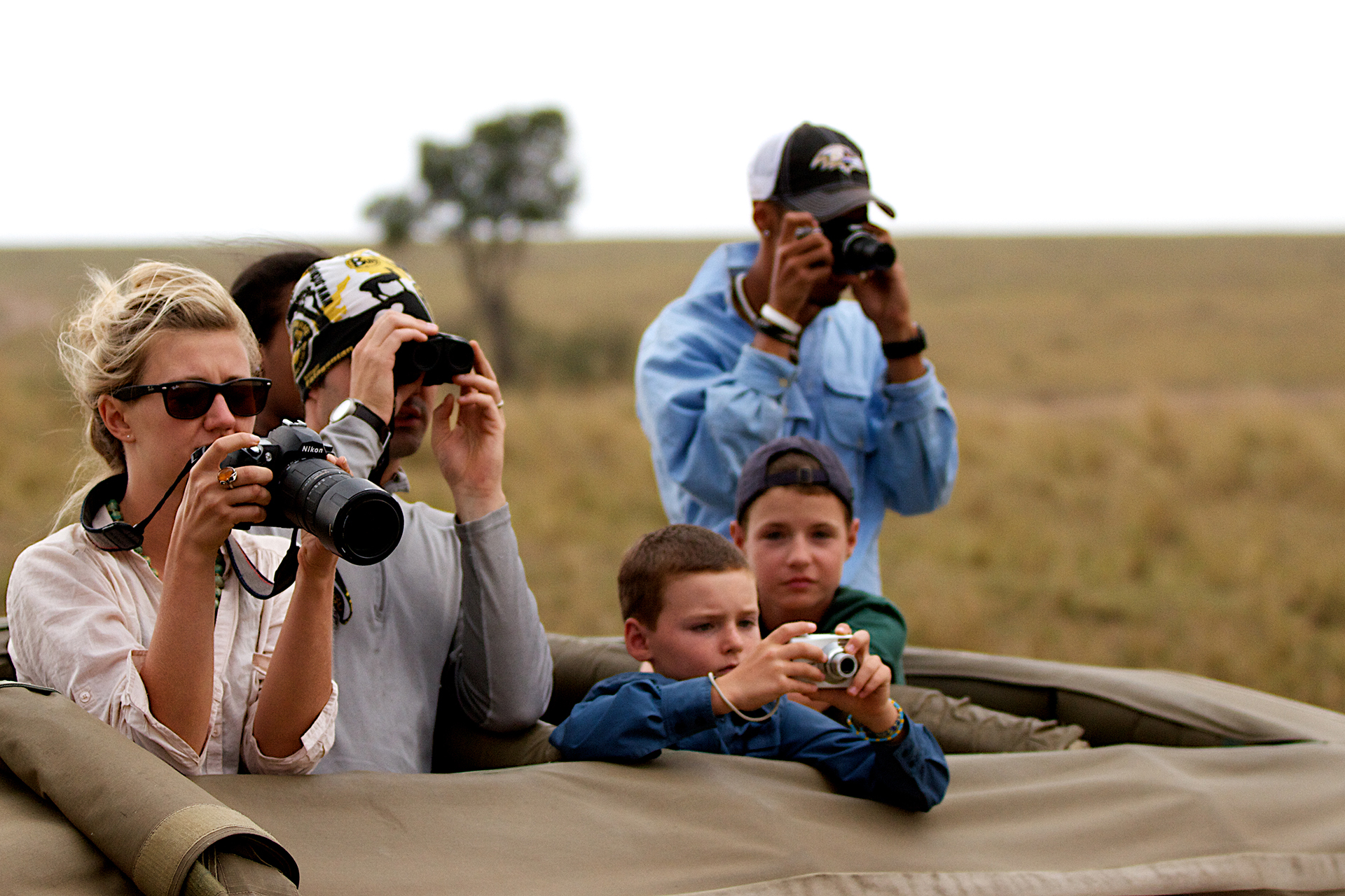 Family taking photos from a car on a Safari