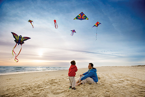 A little boy and his father flying kites on South Padre Island.