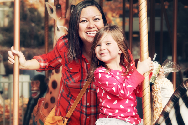A mother and daughter riding a carousel together.