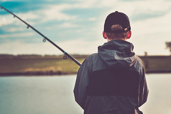 A boy with his fishing pole on the river.