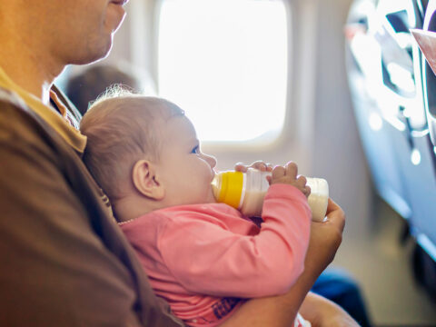 Father holding his baby daughter during flight on airplane going on vacations. Baby girl drinking formula milk from bottle. ; Courtesy of Romrodphoto/Shutterstock