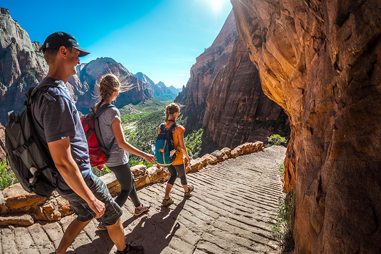 Group of hikers walking down the stairs and enjoying view of Zion National Park; Courtesy Dudarev Mikhail/Shutterstock