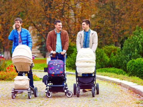 Three fathers walking in the park with strollers