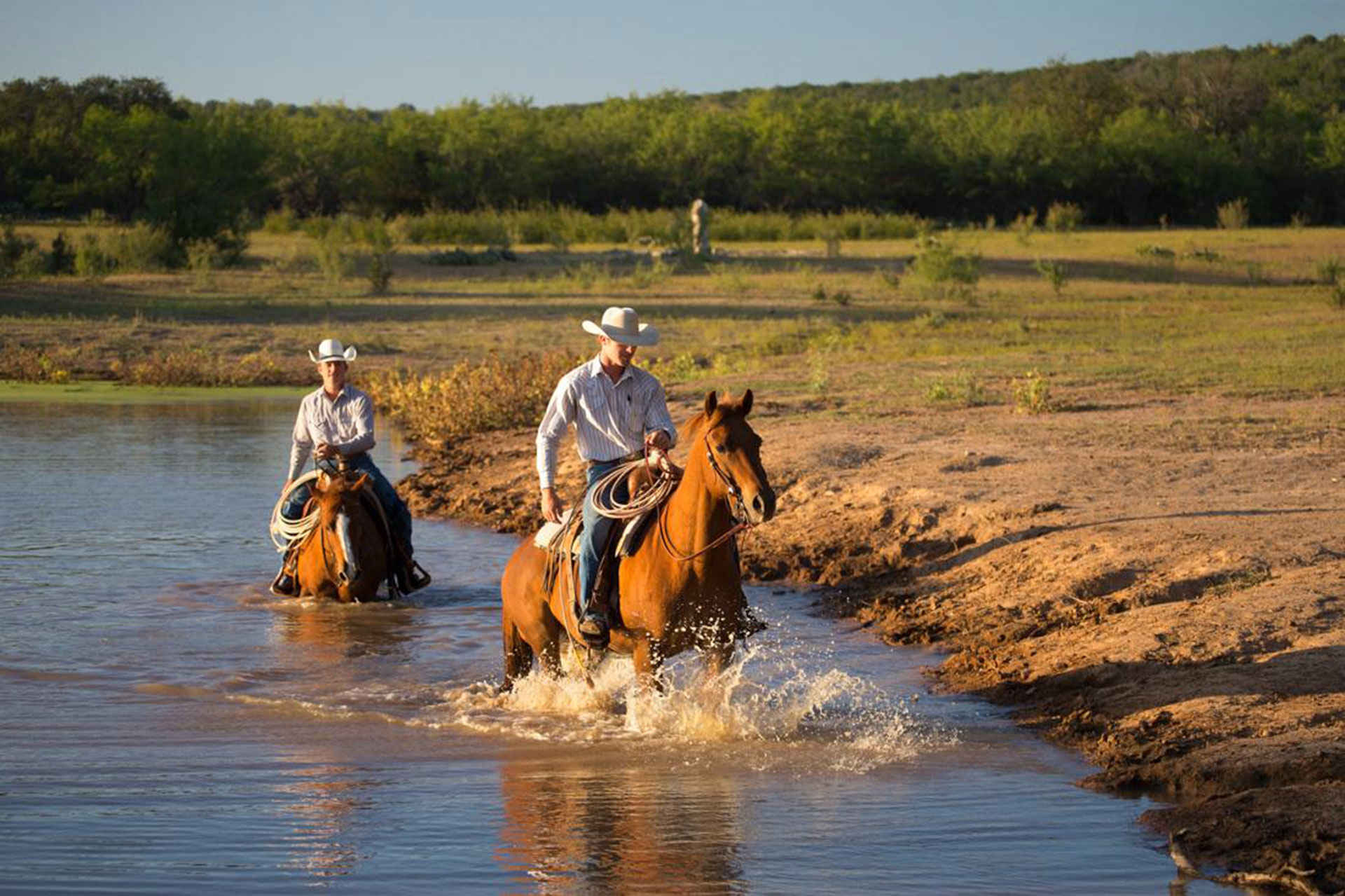 two mean ride a horse at a dude ranch; Photo Courtesy of Wildcatter Ranch Resort & Spa