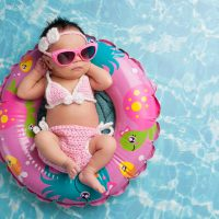Infant Floating in Pool Wearing Sunglasses; Courtesy of Katrina Elena/Shutterstock.com