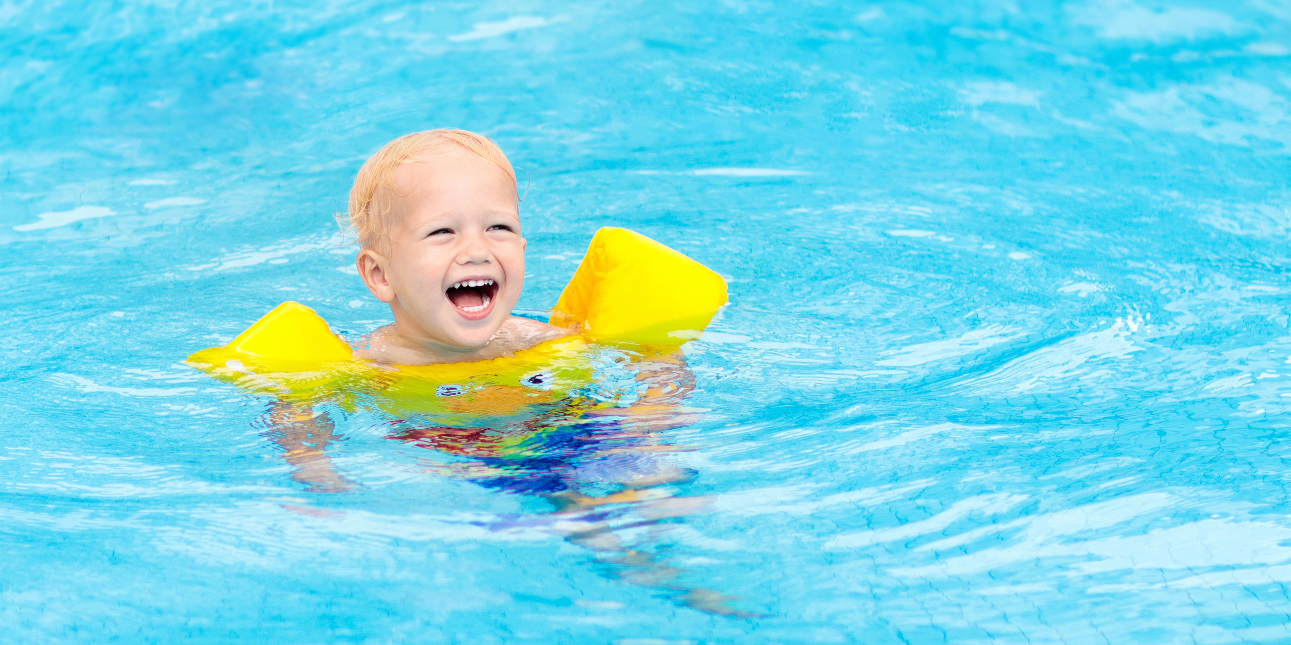 Toddler swimming in pool with swim floaties on; Courtesy of FamVeld/Shutterstock.com