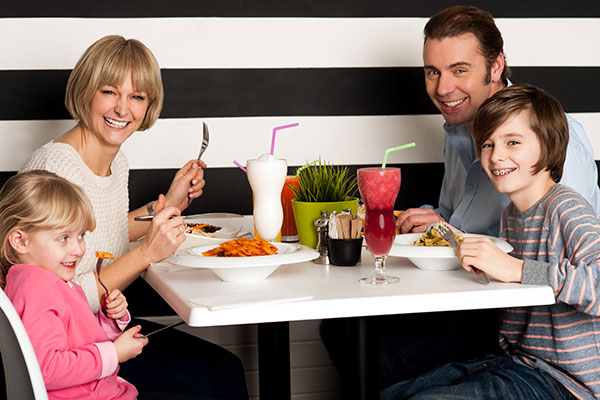 A family of four enjoying a nice meal out.