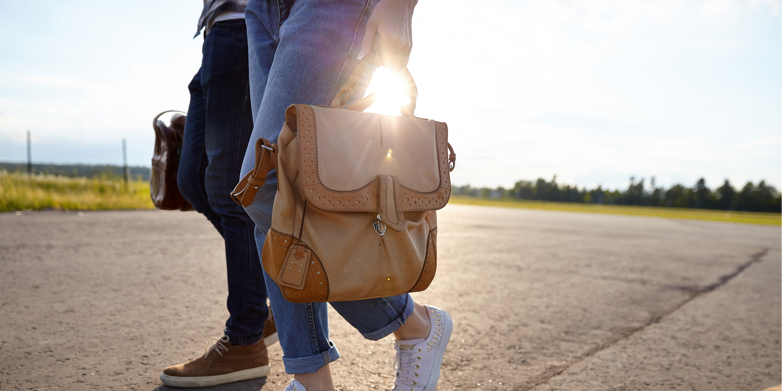 couple walking carrying travel bag runway; Courtesy begalphoto/Shutterstock