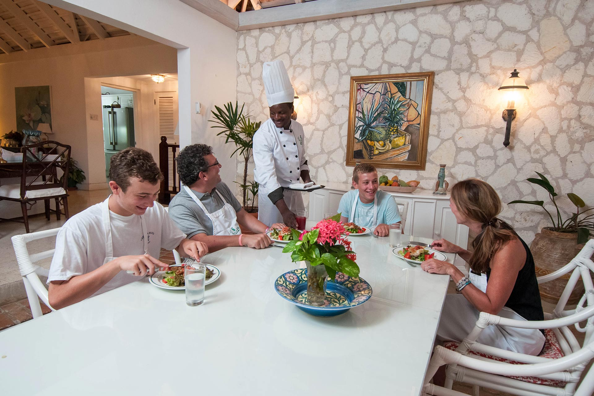 A family enjoying a meal at Round Hill Hotel & Villas in Jamaica.