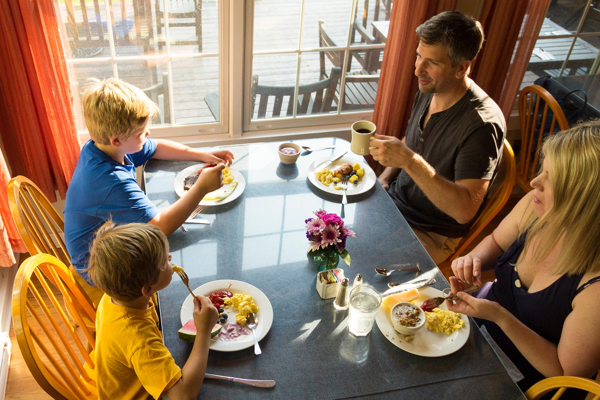 A family sitting down to breakfast at Tyler Place Family Resort in Vermont.