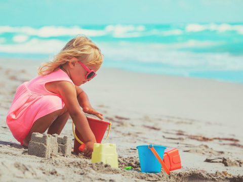 Little Girl Playing with Sand Toys on the Beach;NadyaEugene/Shutterstock.com