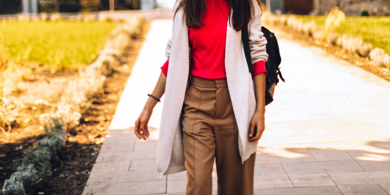 woman walking in park wearing travel pant and backpack; Courtesy of Ekateryna Zubal/Shutterstock