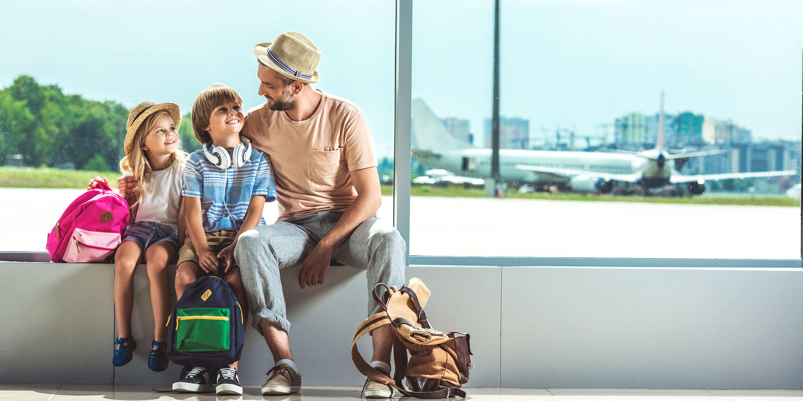 Father and Kids With Carry-On Bags at Airport; Courtesy of LightField Studios/Shutterstock.com