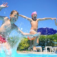 Kids Jumping in Pool; Courtesy of Pavel L Photo and Video/Shutterstock.com