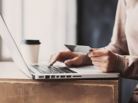 Person making an online purchase with credit card while drinking coffee