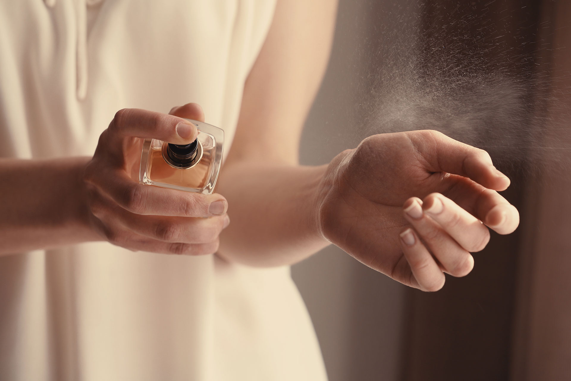 Woman Putting on Perfume; Courtesy of Africa Studio/Shutterstock.com