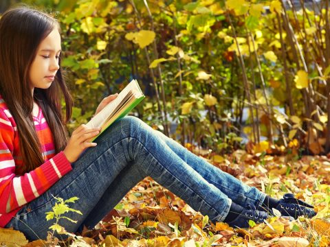 Girl reading outdoors in park.