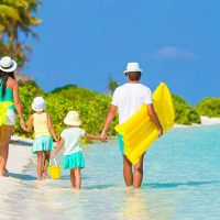 Family Walking on Caribbean Beach; Courtesy of TravnikovStudio/Shutterstock.com