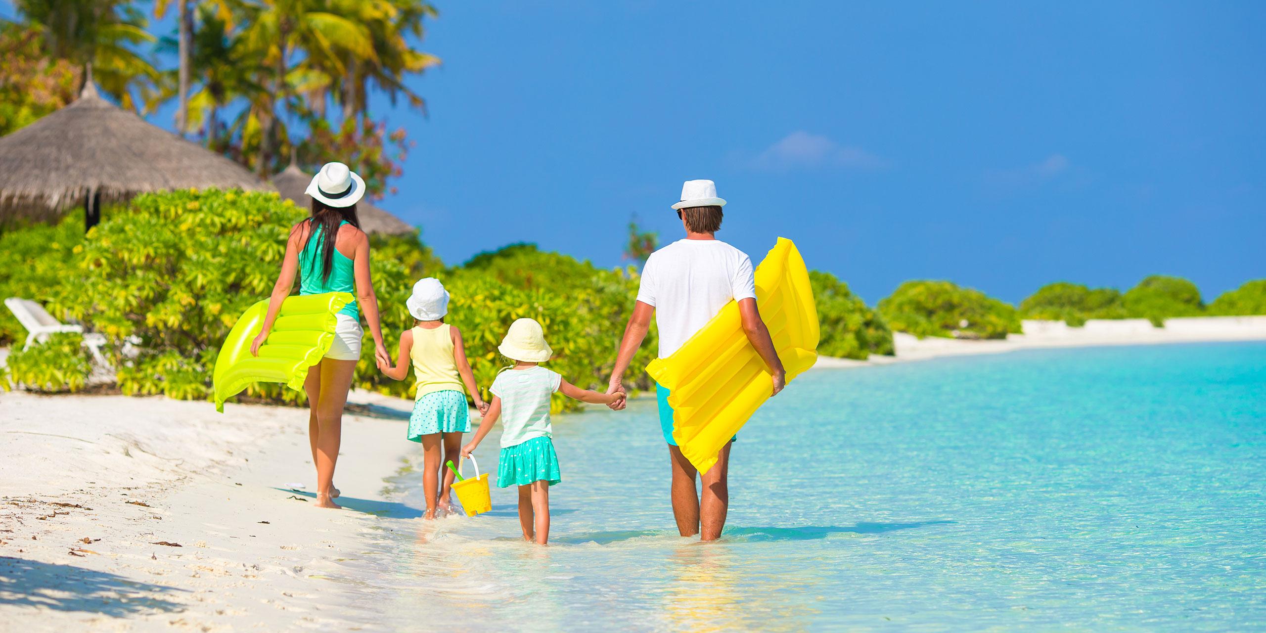 Family Walking on Caribbean Beach; Courtesy of TravnikovStudio/Shutterstock.com