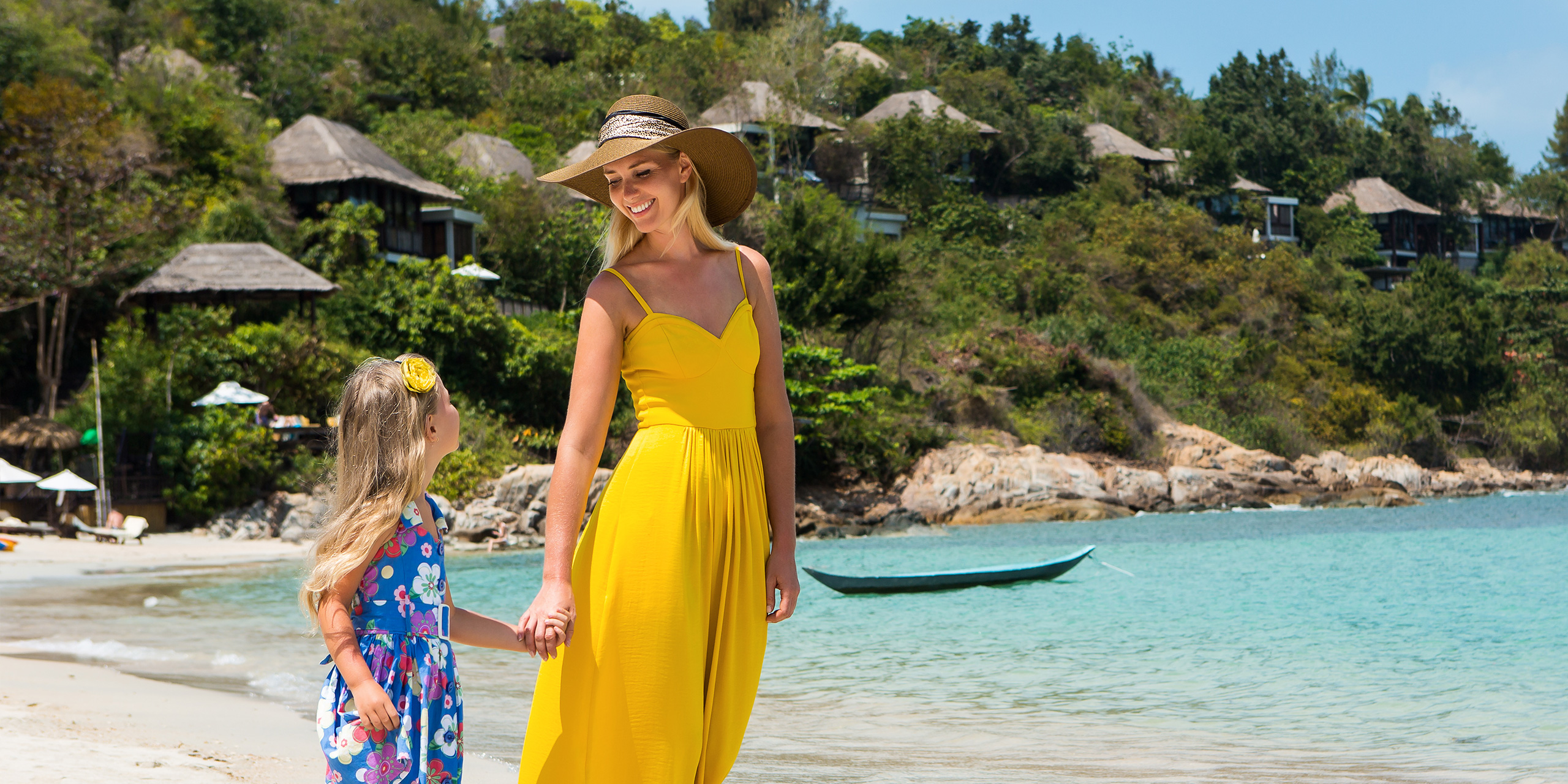 blonde woman in long yellow tunic dress with her pretty little girl in floral dress walking at seaside. ; Courtesy Nikkolia/Shutterstock
